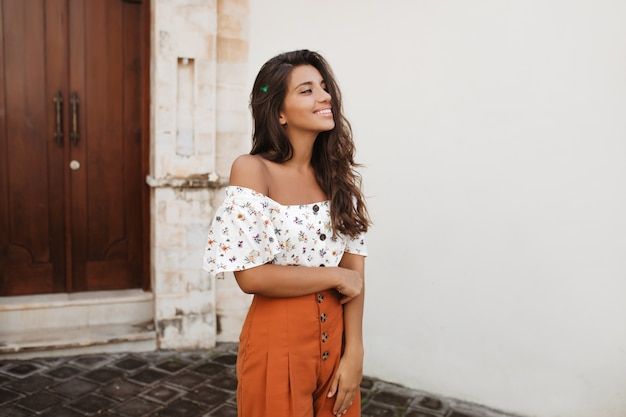 Tanned woman in stylish orange shorts with high waist and light blouse posing against wall of house with antique wooden doors