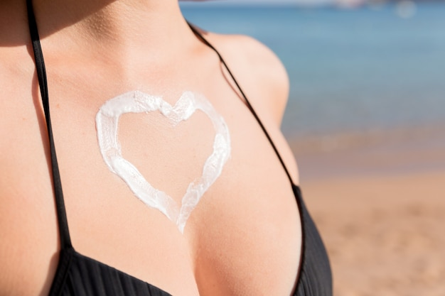 Tanned woman with heart shaped sun cream on her breast at the sea background.