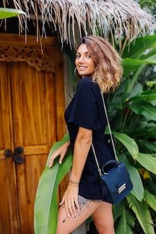 Donna abbronzata con capelli ricci corti in tuta sexy nera vicino alla porta della villa tropicale in vacanza alla luce del tramonto