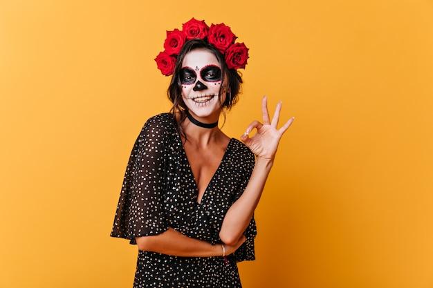 La donna abbronzata con il sorriso bianco come la neve mostra l'approvazione del segno. foto di giovane donna al chiuso con il trucco di halloween su sfondo arancione.