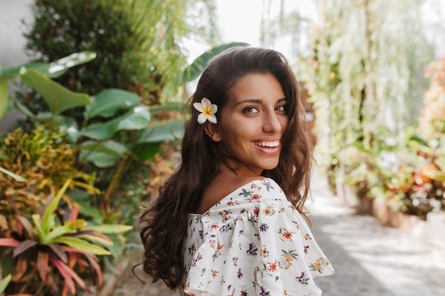 Tanned woman with white flower in wavy dark hair smiles while walking in tropical park