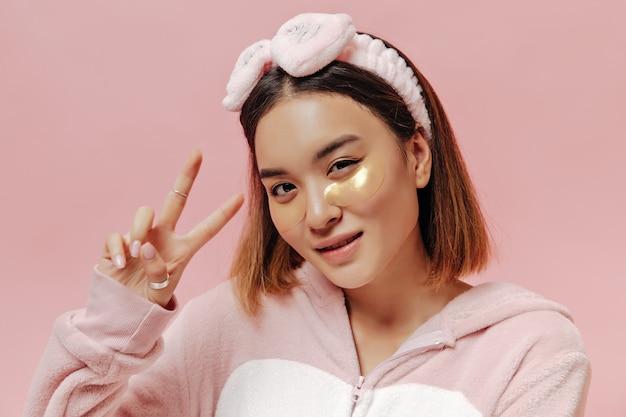 머리띠와 키구루미를 입은 검게 그을린 젊은 아시아 여성은 분홍색 벽에 화장용 안대를 하고 평화 표시를 하고 포즈를 취합니다.