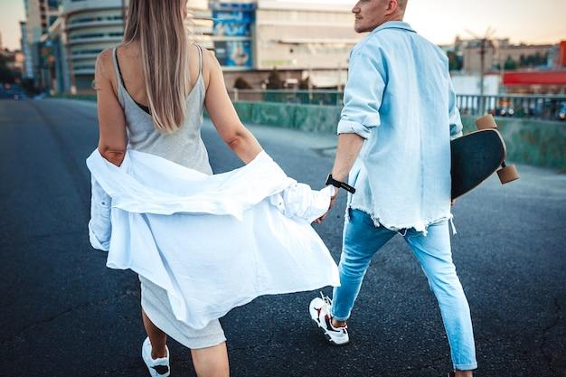 Giovane coppia caucasica abbronzata, storia d'amore moderna con effetto grana della pellicola e stile vintage. ora del tramonto. camminando per le strade della città, calda sera d'estate