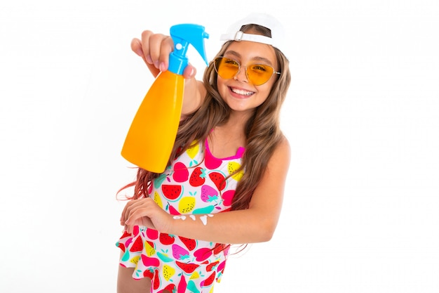 Tanned young girl holding a sunscreen on a white wall
