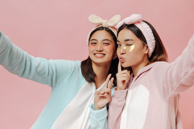 Tanned young women in pajamas, headbands and with cosmetic eyepatches take selfie on pink wall