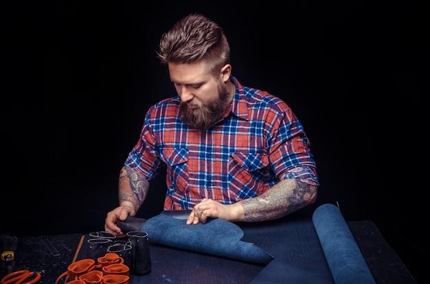Таннер демонстрирует процесс резки кожи в своей кожевенной мастерской