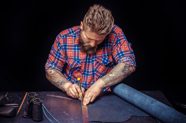 Дубильщик из кожи производит новые изделия из кожи в своей мастерской. / профессиональный дубильщик работает с кожей. Premium Фотографии