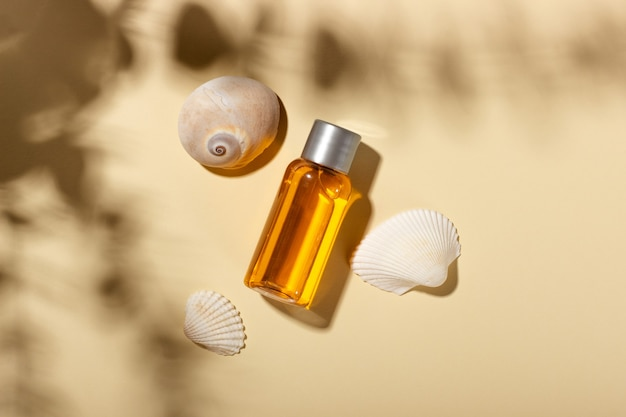 Tanning oil. cosmetic products next to seashells in sunbeams on a pink background. sun protective cosmetics.