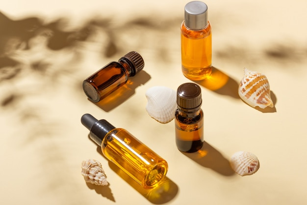 Tanning oil. a set of cosmetics next to seashells in the sunbeams on a pink background. cosmetics for sun protection.