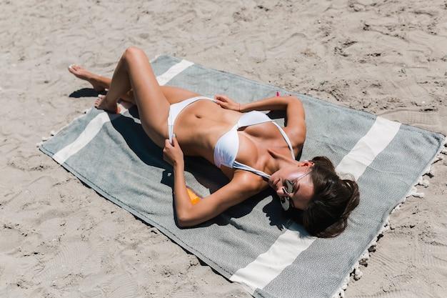 Tanning woman adjusting bikini panties