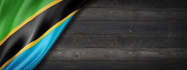 검은 나무 벽에 탄자니아 플래그입니다. 수평 파노라마 배너.