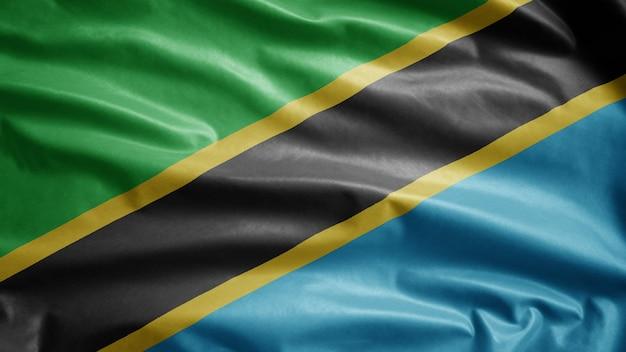 風に揺れるタンザニアの国旗。タンザニアのテンプレートを吹く、柔らかく滑らかなシルクのクローズアップ。布生地テクスチャ少尉背景