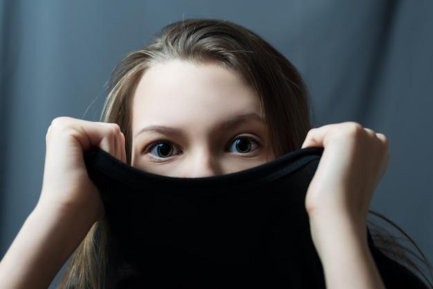 Tâ•tシャツの下に隠れているティーンエイジャーの女の子