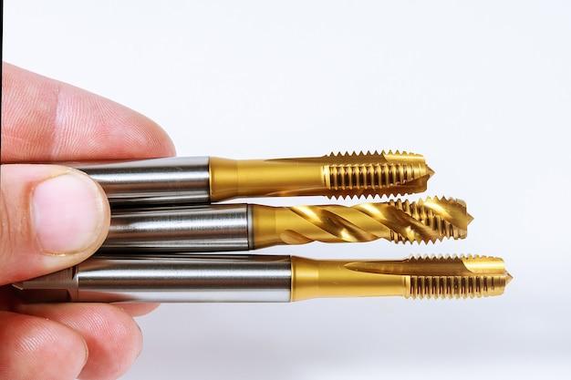Метчик для нарезания резьбы в металле на белом фоне. инструмент для обработки металла.
