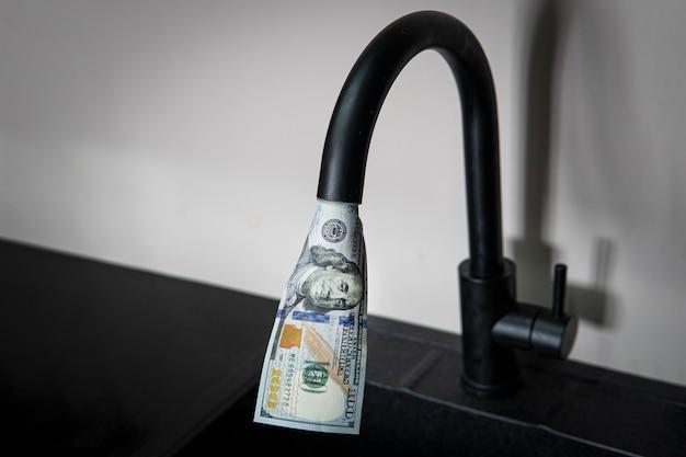 Нажмите, из него текут доллары. дорогое водоснабжение. концепция повышения стоимости коммунальных услуг для населения. дорогая горячая и холодная вода дома.