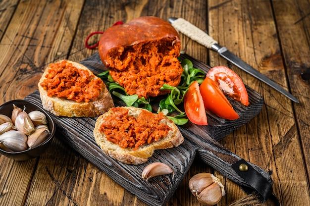 나무 도마에 소브라사다 경화 돼지고기 소시지와 토마토를 곁들인 타파 샌드위치. 나무 배경입니다. 평면도.