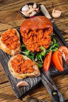 木製のまな板にソブラサーダで塩漬けしたポークミートソーセージとトマトを添えたタパアサンドイッチ
