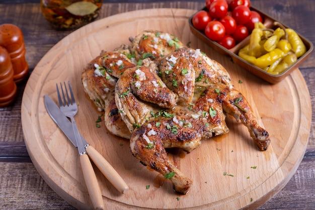 Цыплята тапака (табака) с помидорами черри, пепперони, чесноком и кинзой на деревянной доске. традиционное грузинское блюдо. крупный план.