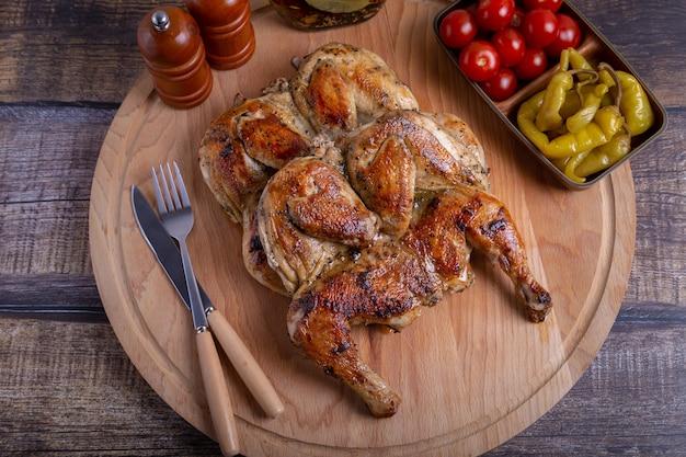 Цыпленок тапака табака с помидорами и пепперони на деревянной доске традиционное грузинское блюдо