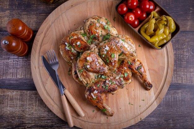 Тапака табака цыплята с помидорами пепперони, чесноком и кинзой на деревянной доске традиционное грузинское блюдо