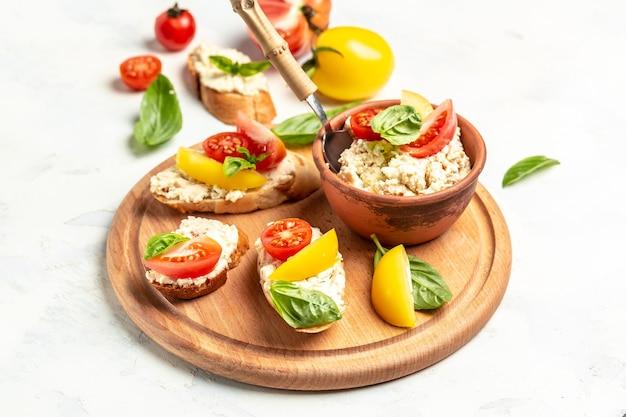 Тапас, закуски с нарезанными овощами, помидорами, сливочным сыром и листьями базилика. на жареном багетном хлебе. чистое питание, диета, концепция веганского питания. вид сверху