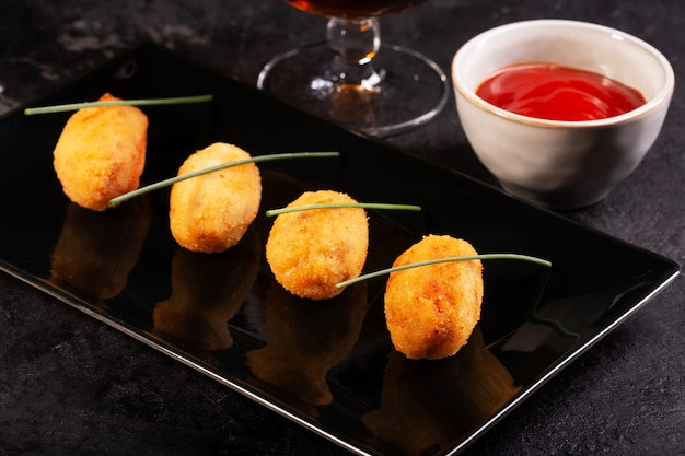 Tapas croquettes, traditional spanish or french snack with red sauce