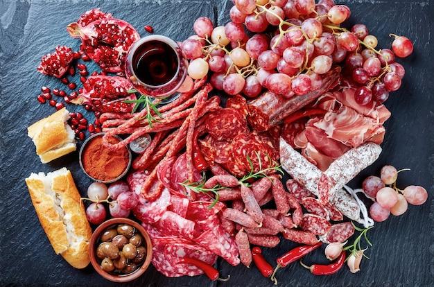 Выбор тапас. каменная разделочная доска с мясными закусками. испанское вяленое мясо, хамон, чисторра, чоризо