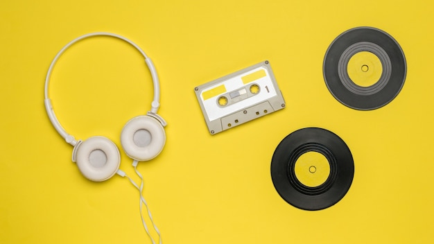 黄色の背景にテープカセット、ヘッドフォン、ビニールレコード。オーディオ録音を保存および再生するためのレトロなデバイス。