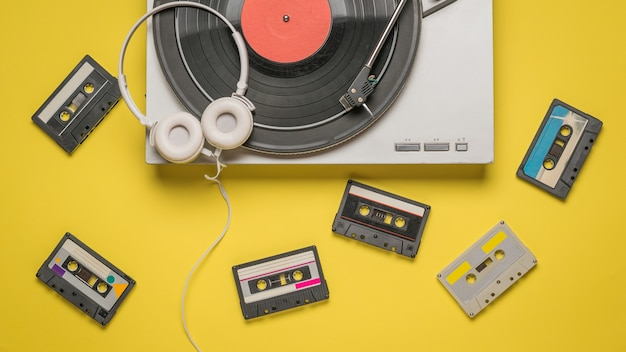 Tape cassettes, a vinyl record player, and headphones on yellow