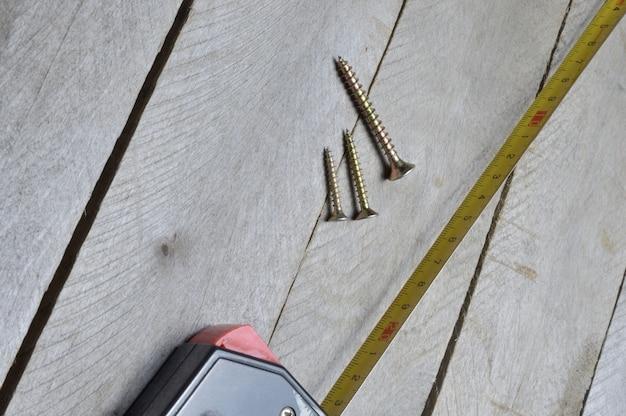 巻尺とネジは木製の背景にあります。閉じる。