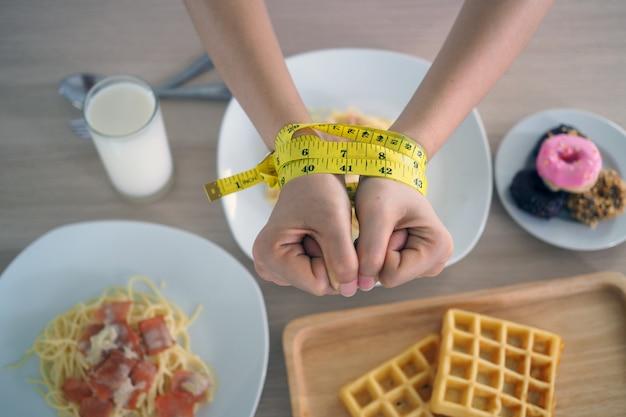 女性の腕の周りの巻尺。トランス脂肪、スパゲッティ、ドーナツ、ワッフル、お菓子を食べるのをやめます。健康のために体重を減らす。トップビューダイエットコンセプト