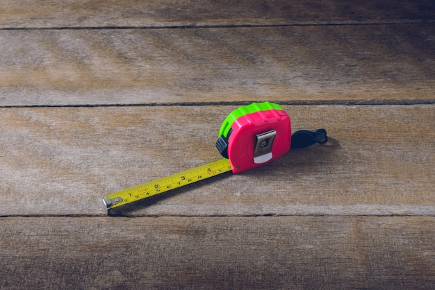Tape measure on the brown wooden background