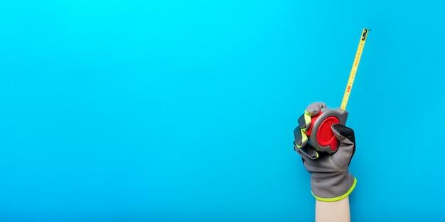줄자. 파란색 배경에 줄자를 들고. 수리 및 설치 도구. 건설 주제의 디자인 및 인쇄를 위한 배너입니다.