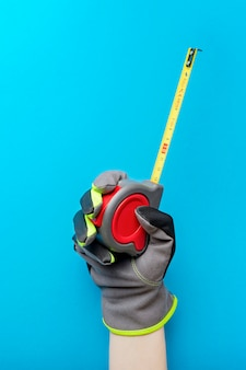 Tape measure. holding a tape measure on a blue background. repair and installation tool. vertical photo for the design and printing of construction topics.