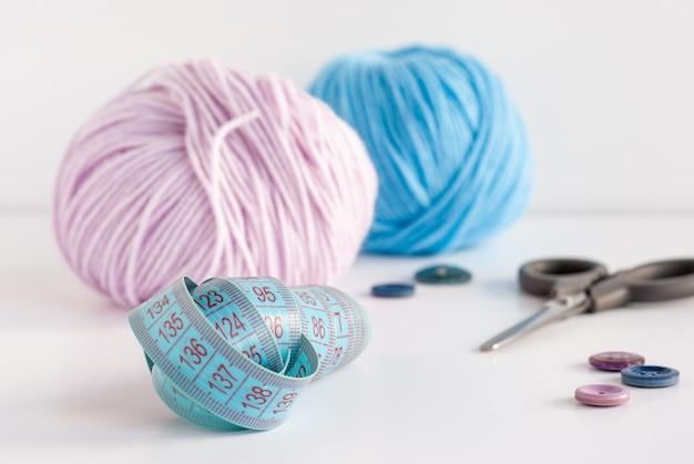 흰색 테이블에 아기 원사, 가위 및 바느질 단추의 줄자, 분홍색 및 파랑 skeins