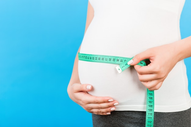 Tape measure on pregnant womans belly