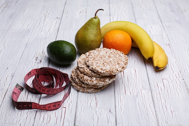 Tape-measure, rice cookies, avokado, pear, orange and bananas lie on the wooden table