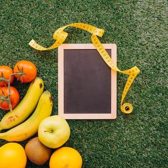 Misura di nastro su ardesia accanto ai frutti