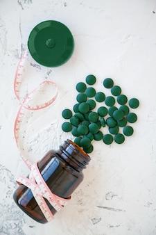 緑のスピルリナの丸薬のボトルで巻尺