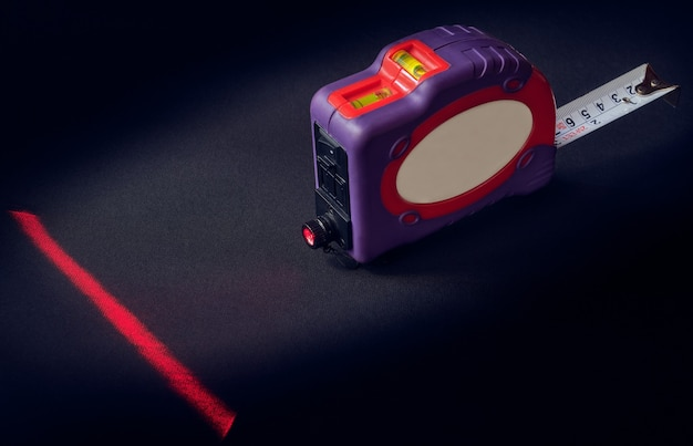 Tape measure with laser level on dark space, small depth of sharpness