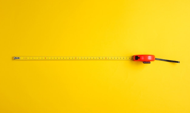 Tape measure on yellow. top view.