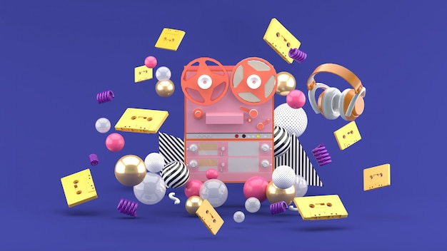 Tape recorder among the tapes and headphones on the purple. 3d rendering.