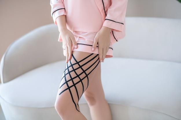 테이프. 그녀의 다리에 테이프를 넣어 핑크 란제리에 여자