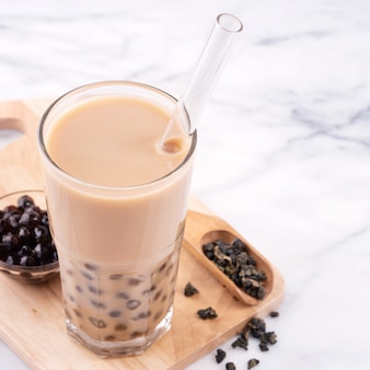 Tapioca pearl ball bubble milk tea, popular taiwan drink, in drinking glass with straw on marble white table and wooden tray, close up, copy space.