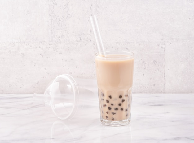 Tapioca pearl ball bubble milk tea, popular taiwan drink, in drinking glass with straw on marble white table and wooden tray