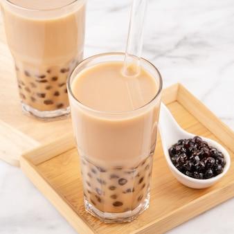 タピオカパールボールバブルミルクティー、人気の台湾ドリンク、大理石の白いテーブルと木製トレイにストローでグラスを飲み、クローズアップ、コピースペース。