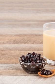 タピオカパール、お茶やその他の飲料用のバブルトッピングをカップに入れ、木製のテーブルに置きます。コピースペース