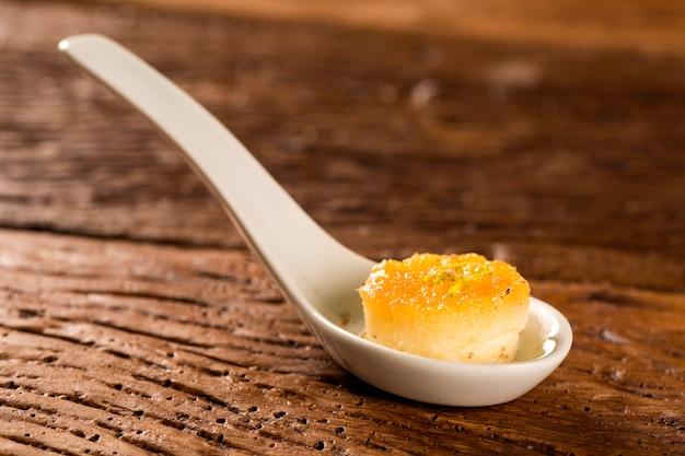 Пудинг из тапиоки с тиражом - приправой из региона амазонки в ложке. вкус гастрономической еды руками
