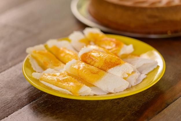테이블에 노란색 접시에 녹은 치즈와 타피오카. 브라질 요리법.