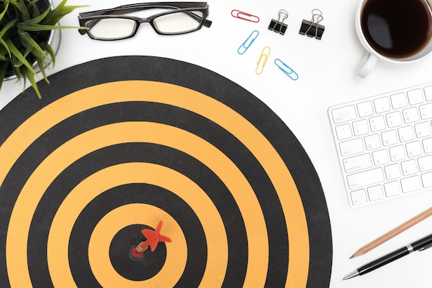 Target arrow hitting on bullseye over office desk table
